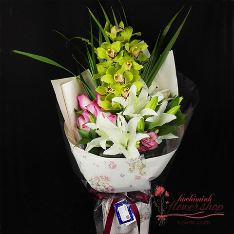 A flower bouquet with orchid and white lilies